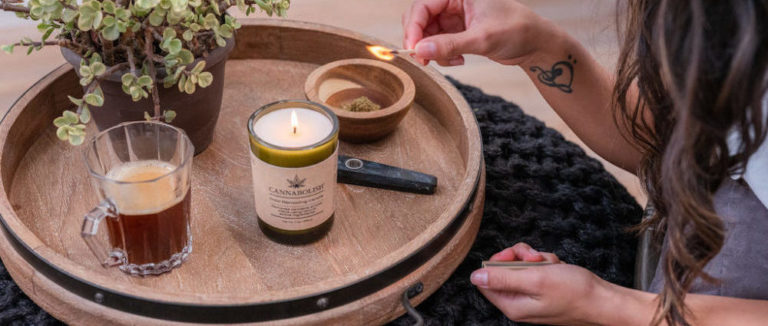 Person lighting a Cannabolish candle with tea next to it